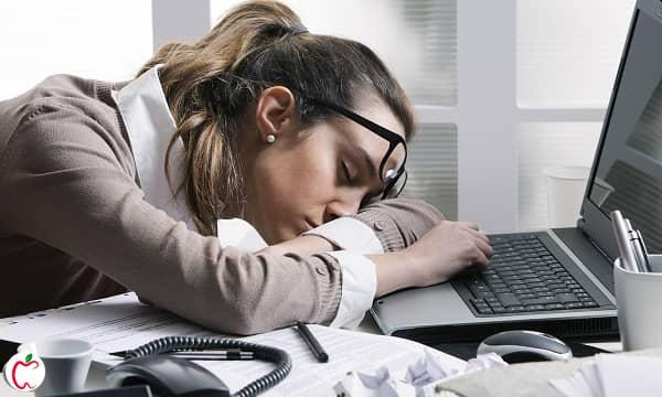 زن جوان خوابیده برروی لپتاپ در محل کار