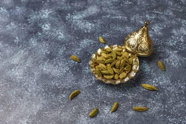 دانه های هل در ظرف زیبای مسی ، فواید و مضرات هل در غذا و چای   سیوطب