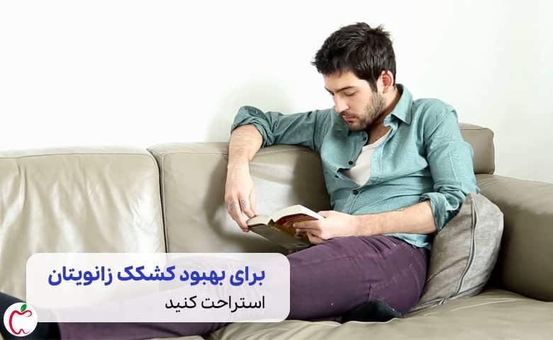 درمان کشکک زانو |  مردی پاهایش را دراز کرده و مشغول کار کردن با گوشی همراه است سیوطب